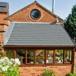 Conservatory with sloped roof grey tiled roof with circular window