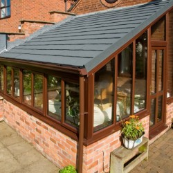 Red brick conservatory with brown window frames and sloped grey roof tiles