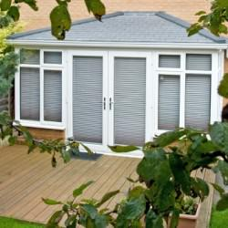 White Conservatory with Grey Tiled roof with blinds shut