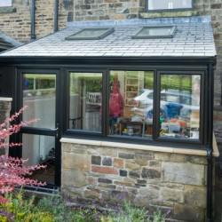 Stone Conservatory with grey tiled roof and two skylights