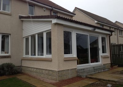 Sloped Conservatory with cream stones white window and brown roof