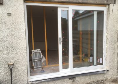 patio doors open with work being carried out inside