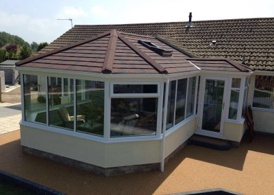 Conservatory with Brown roof and orange driveway