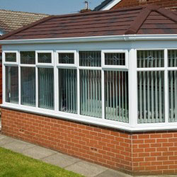 Red Brick Conservatory with White windows and Brown and Black Roof Tiles