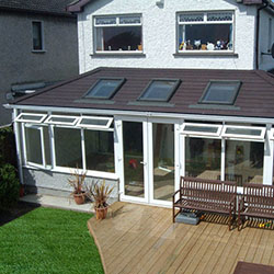 Double hipped conservatory with brown roof with light brown deck