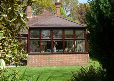 Large Conservatory with brown window frame and brown roof